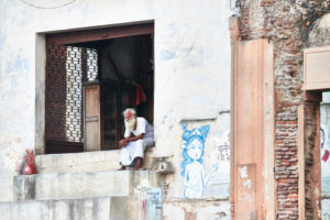 Man sitting in entrance, looking in the distance, graffiti, India, Vrindavan