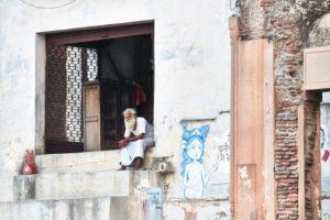 Mann sitzt in Eingang, schaut in die Ferne, Graffiti, Indien, Vrindavan