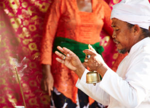 Priester, segnet, sprenkelt Wasser, weißes Gewand, Blick zur Seite, Reportage, traditionelle Hochzeit, Bali, Indonesien, Asien