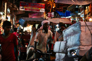 Rickshaw driver, loaded, Evening mood, many people, full streets Delhi, shops, India