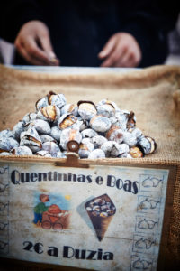 roasted sweet chestnuts, seller, cropped hands, Lisbon, Portugal