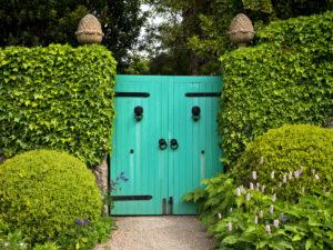 Irland, Donegal, Glenveagh Nationalpark, Gartenanlage von Glenveagh Castle, grünes Gartentor, Gartenmauer, blühender Knöterich