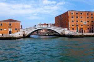 Blick vom Kanal auf Uferpromenade mit Brücke in Venedig