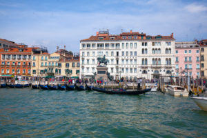 View from the canal on waterfront with gondolas in Venice