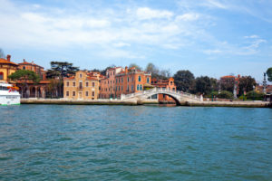 View from the canal on waterfront with bridge in Venice