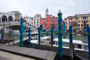 Bootsanlegestelle mit Rialtobrücke und Hausfassaden in Venedig