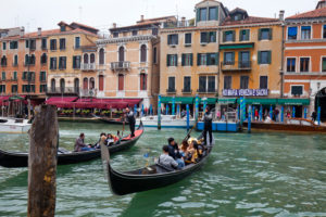 Gondolas on the Grand Canal in front of waterfront in Venice