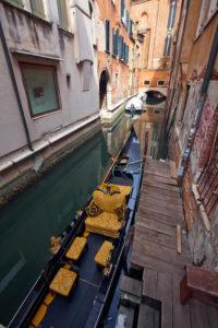 schmaler Kanal mit Gondel zwischen Häusern in Venedig