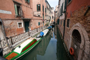 narrow canal with boats between houses in Venice