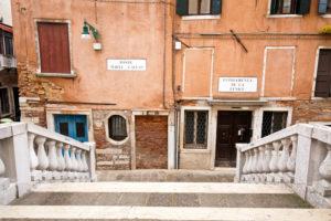 steinerne Brücke vor verblichener Hausfassade in Venedig