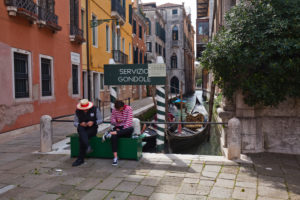 two gondoliers are waiting for guests and are looking at their cell phones in Venice
