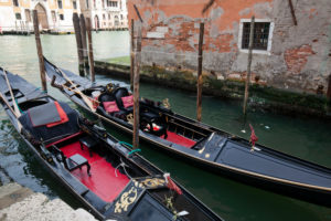 two black gondolas lie in narrow canal in Venice