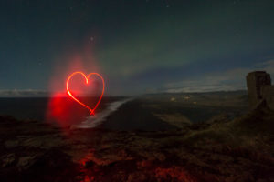 Iceland, flashlight painted red heart, night, northern lights, starry sky, volcano in the background,