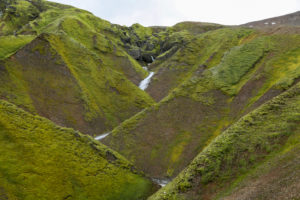 Iceland, Fjallabak, torrent in a zigzag, green mountainside