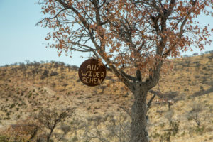 Sign with 'Auf Widersehen' (good bye) in a tree in the Himba country, Namibia