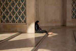 Einheimische Frau sitzt barfuß in in der Vorhalle der Hassan-II. Moschee, Casablanca, Marokko