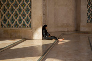 Local woman sits barefoot in in the vestibule of the Hassan-II. Mosque, Casablanca, Morocco