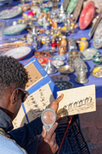 Ait Benhaddou, artist vendor, creative, Morocco, solar energy, power, commerce, young man, magnifying glass