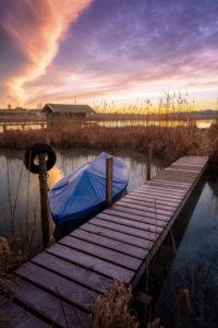 Steg und Boot am Seeufer in der Morgendämmerung