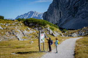 Man and woman hiking on road sign at Osterfelder at the foot of the Alpspitze, in the background the Wetterstein Mountains, blue sky, hiking trail, Garmisch-Partenkirchen, Upper Bavaria, Bavaria, southern Germany, Germany