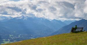 Person on bench enjoys view from Wank towards Berg Daniel (Austria), view over Garmisch-Partenkirchen, Upper Bavaria, Bavaria, southern Germany, Germany