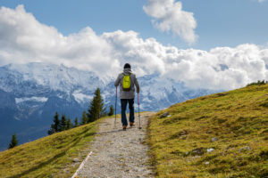 Man hikes on hiking trail at the Wank in Garmisch-Partenkirchen, looking towards the Wetterstein Mountains, blue sky, clouds, Upper Bavaria, Bavaria, southern Germany, Germany
