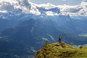 Man enjoys view from the Wank over Garmisch-Partenkirchen, view towards the Wetterstein Mountains with Alpspitze, Waxensteinen and Zugspitze, Garmisch-Partenkirchen, Upper Bavaria, Bavaria, Southern Germany, Germany