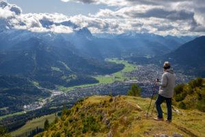 Man enjoys view from the Wank over Garmisch-Partenkirchen, view towards the Wetterstein Mountains with Alpspitze, Waxensteinen and Zugspitze and Berg Daniel (Austria), Garmisch-Partenkirchen, Upper Bavaria, Bavaria, southern Germany, Germany