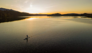 Aerial view of woman with stand up paddle (SUP) on Staffelsee at sunset, Murnau, blue country, Garmisch-Partenkirchen, Upper Bavaria, Bavaria, southern Germany, Germany