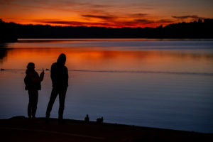 Silhouette of young woman and young man after sunset at Staffelsee in Murnau, blue country, Garmisch-Partenkirchen, Upper Bavaria, Bavaria, southern Germany, Germany