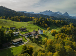Wamberg with St. Anna's Church in autumn, aerial view with a view along the walk towards the Wetterstein Mountains with Alpspitze, Zugspitze and Waxensteine, blue sky, veil clouds, trees, Garmisch-Partenkirchen, Upper Bavaria, Bavaria, southern Germany, Germany