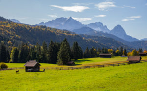 Autumn shot of Holzstadel with horses against Wetterstein Mountains with Alpspitze, Zugspitze and Waxenstones, blue sky, clouds, trees, fence, Garmisch-Partenkirchen, Upper Bavaria, Bavaria, southern Germany, Germany