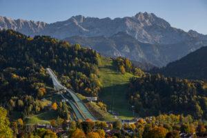 Large Olympic ski jump in Garmisch-Partenkirchen in autumn against Gudiberg and Partenkirchner Dreitorspitze in the Wetterstein Mountains, blue sky, trees, Garmisch-Partenkirchen, Upper Bavaria, Bavaria, southern Germany, Germany