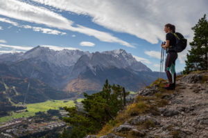Young woman hiking towards Kramer looks out over Garmisch-Partenkirchen and Wetterstein Mountains with Alpspitze, Zugspitze, and Waxensteine, blue sky, clouds, trees, Garmisch-Partenkirchen, Upper Bavaria, Bavaria, southern Germany, Germany