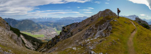 Panoramic photo of young woman hiking towards Kramer with a view over Garmisch-Partenkirchen, Ester Mountains, Karwendel Mountains and Wetterstein Mountains with Zugspitze, blue sky, clouds, hiking trail, rock, Garmisch-Partenkirchen, Upper Bavaria, Bavaria, southern Germany, Germany