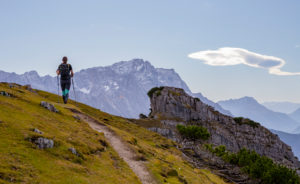 Young woman hiking towards Kramer with a view of the Wetterstein Mountains (with Zugspitze), blue sky, clouds, hiking trail, rock, Garmisch-Partenkirchen, Upper Bavaria, Bavaria, southern Germany, Germany