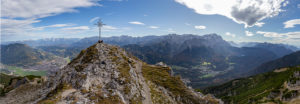 Panoramic photo from the Kramer summit with a view over Garmisch-Partenkirchen and Grainau, Ester Mountains, Karwendel Mountains and Wetterstein Mountains (with Alpspitze and Zugspitze) and Ammergau Alps, blue sky, clouds, rock, summit cross, Garmisch-Partenkirchen, Upper Bavaria, Bavaria, southern Germany, Germany