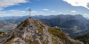 Panoramic photo from the Kramer summit with a view over Garmisch-Partenkirchen, Grainau, Karwendel Mountains and Wetterstein Mountains (with Alpspitze and Zugspitze), blue sky, clouds, rock, summit cross, Garmisch-Partenkirchen, Upper Bavaria, Bavaria, southern Germany, Germany
