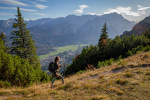 Young woman hiking towards Kramer in autumn with a view over Garmisch-Partenkirchen and Wetterstein Mountains with Alpspitze, Zugspitze, and Waxensteine, blue sky, clouds, hiking trail, trees, Garmisch-Partenkirchen, Upper Bavaria, Bavaria, southern Germany, Germany