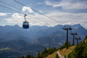 Two people in a historic gondola on the Wank with a view over the Wetterstein Mountains with Alpspitze, Zugspitze and Waxensteine, blue sky, clouds, mountain railway, Garmisch-Partenkirchen, Upper Bavaria, Bavaria, southern Germany, Germany