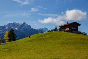 Man walks on meadow towards mountain hut at Eckbauer in autumn, in the background the Wetterstein Mountains with Alpspitze and Zugspitze, blue sky, clouds, Garmisch-Partenkirchen, Upper Bavaria, Bavaria, southern Germany, Germany