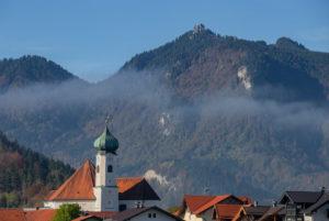 Parish Church of St. Clemens in Eschenlohe in autumn against Ettaler Manndl (Ammergau Alps), mist, blue sky, trees, Garmisch-Partenkirchen, Upper Bavaria, Bavaria, southern Germany, Germany
