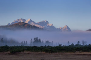 Clouds of fog on the Barmsee against Wetterstein Mountains with Alpspitze, Zugspitze and Waxenstones, autumn, trees, blue sky, Krün, Garmisch-Partenkirchen, Upper Bavaria, Bavaria, southern Germany, Germany