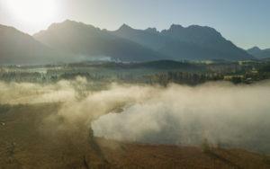 Aerial view mist at the Barmsee against the Karwendel mountains, blue sky, trees, lake shore, sun, back light, Krün, Garmisch-Partenkirchen, Upper Bavaria, Bavaria, southern Germany, Germany