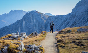 Man hiking at the foot of the Alpspitze with a view towards the Bernadeinkopf in the Wetterstein Mountains, blue sky, hiking trail, Garmisch-Partenkirchen, Upper Bavaria, Bavaria, southern Germany, Germany