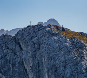 Person hiking just before the summit cross at Bernadeinkopf at the foot of the Alpspitze in the Wetterstein Mountains, blue sky, rock, Garmisch-Partenkirchen, Upper Bavaria, Bavaria, southern Germany, Germany