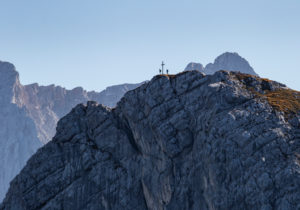 Two people at the summit cross at the Bernadeinkopf at the foot of the Alpspitze in the Wetterstein Mountains, blue sky, rock, Garmisch-Partenkirchen, Upper Bavaria, Bavaria, southern Germany, Germany