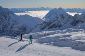Two young skiers just before setting off on the Zugspitze in winter, looking towards the southeast, high fog, snow, mountain peaks, blue sky, Zugspitze, Grainau, Garmisch-Partenkirchen, Upper Bavaria, Bavaria, southern Germany, Germany