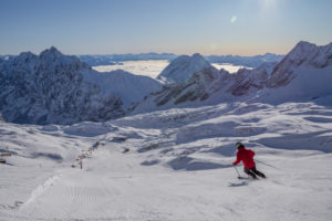 Skiers on the Zugspitze in winter while skiing on the slopes, looking towards the southeast, blue sky, high fog, snow, mountain peaks, Zugspitze, Grainau, Garmisch-Partenkirchen, Upper Bavaria, Bavaria, southern Germany, Germany
