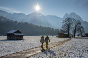 Man and woman on a winter walk on a dirt road in Garmisch-Partenkirchen, looking towards the Wetterstein Mountains with the Alpspitze and wax stones, wooden sticks, blue sky, sun, back light, trees, meadow, walking path, Garmisch-Partenkirchen, Upper Bavaria, Bavaria, southern Germany, Germany